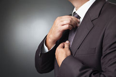 Businessman in black costume tie one's necktie Royalty Free Stock Photo
