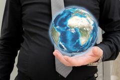 Businessman in black shirt and gray necktie holding globe royalty free stock photography