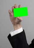 Businessman in a black suit and black tie holding a card, a hand holding a card, green card, card is inserted, the green chroma. Key studio Stock Image