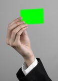 Businessman in a black suit and black tie holding a card, a hand holding a card, green card, card is inserted, the green chroma. Key studio Royalty Free Stock Photo
