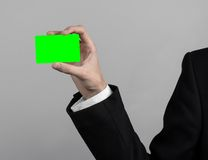 Businessman in a black suit and black tie holding a card, a hand holding a card, green card, card is inserted, the green chroma. Key studio Royalty Free Stock Image