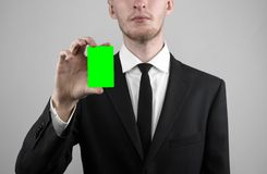 Businessman in a black suit and black tie holding a card, a hand holding a card, green card, card is inserted, the green chroma Royalty Free Stock Images