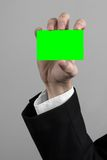 Businessman in a black suit and black tie holding a card, a hand holding a card, green card, card is inserted, the green chroma Royalty Free Stock Photography