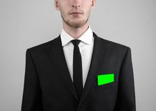 Businessman in a black suit and black tie holding a card, a hand holding a card, green card, card is inserted, the green chroma Stock Image