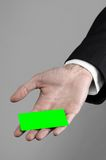 Businessman in a black suit and black tie holding a card, a hand holding a card, green card, card is inserted, the green chroma. Key studio Stock Photo