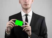 Businessman in a black suit and black tie holding a card, a hand holding a card, green card, card is inserted, the green chroma. Key studio Royalty Free Stock Images