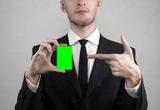 Businessman in a black suit and black tie holding a card, a hand holding a card, green card, card is inserted, the green chroma. Key studio Royalty Free Stock Photography
