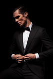 Businessman in black suit with bowtie posing seated in dark Royalty Free Stock Photo