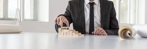 Businessman in black suit building steps of wooden blocks. In a wide panorama view Stock Image