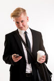 Businessman in black suit with coffee mug and phone Royalty Free Stock Photos
