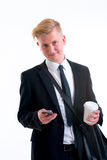 Businessman in black suit with coffee mug and phone Stock Photos