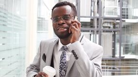 Businessman in black suit drinking takeaway coffee and use smartphone in modern office