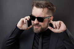 A businessman in a black suit and glasses is talking on the phone. He does not hear his interlocutor, so he plugs his free ear wit Royalty Free Stock Images