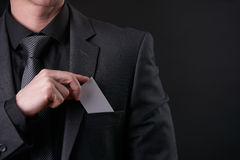 Businessman in black suit and gray necktie put or take out visit card in pocket Royalty Free Stock Image