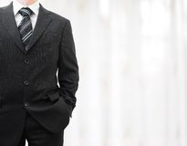 Businessman in black suit with hand in pocket with blurred backg Royalty Free Stock Photography