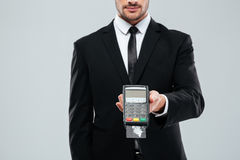 Businessman in black suit holding bank terminal with credit card Royalty Free Stock Images