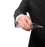 Businessman in a black suit holding a key Stock Photography