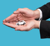 Businessman in black suit holding small car model Stock Image