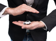 Businessman in black suit holding small car model Stock Photos