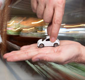 Businessman in black suit holding small car model Royalty Free Stock Image