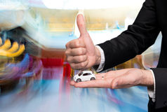 Businessman in black suit holding small car model and showing ok Stock Photo