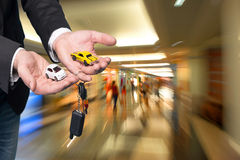 Businessman in black suit holding small car models Royalty Free Stock Photos