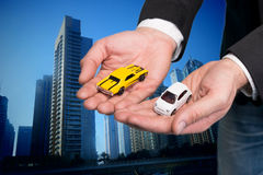 Businessman in black suit holding two small car models Stock Images