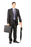 Businessman in black suit holding an umbrella and briefcase Royalty Free Stock Photography
