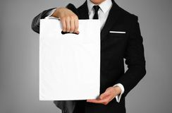 Businessman in a black suit holding a white plastic bag. Close up. Isolated background royalty free stock photography