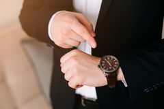 Businessman in black suit look at his expensive swiss wristwatch on his hand and watching the time Royalty Free Stock Photo