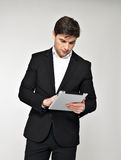 Businessman in black suit with pad at studio Royalty Free Stock Photo