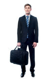 Businessman in black suit posing with bag Stock Photography