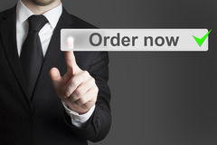 Businessman in black suit pushing button order now Stock Photo