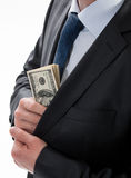 A businessman in a black suit putting money in his pocket Stock Photos
