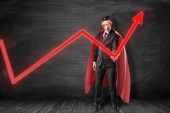 Businessman in black suit, red cape and red mask with glaring white eyes holding with one hand red graph arrow pointing. Up at black graph ruled wall. Business stock photography