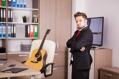 Businessman in black suit and red tie posing. In front of his desk in the office. There is a guitar in the background on the chair Royalty Free Stock Photos