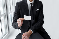 Businessman in black suit showing is card Royalty Free Stock Photo