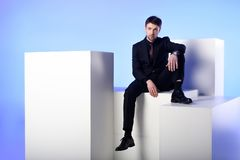 businessman in black suit sitting on white block royalty free stock photos