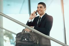 Businessman in black suit speaking over mobile or smart phone. With business partners Royalty Free Stock Photography