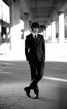 Businessman in black suit standing on street under bridge Stock Photography