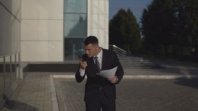 Businessman in black suit talking on smartphone and throw out documents against business building background outdoor stock footage