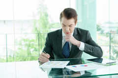 Businessman in black suit use tablet and read report in office Royalty Free Stock Images