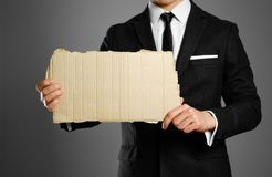 Businessman in a black suit, white shirt and tie holding a piece. Of cardboard. Clean empty paper for your text Stock Photo