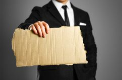 Businessman in a black suit, white shirt and tie holding a piece. Of cardboard. Clean empty paper for your text Royalty Free Stock Photos