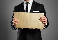 Businessman in a black suit, white shirt and tie holding a piece. Of cardboard. Clean empty paper for your text Stock Photos