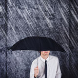 Businessman with black umbrella protecting from rain Stock Photos