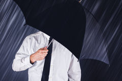 Businessman with black umbrella protecting from rain Stock Photo
