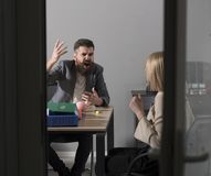 Businessman blame financier in money crisis. Angry boss shout at accountant in office. Bearded man and woman discuss stock photo