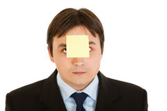 Businessman with blank adhesive note over mouth. Young businessman with blank adhesive note over his mouth isolated on white Royalty Free Stock Photo
