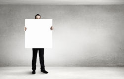 Businessman with blank banner  . Mixed media Royalty Free Stock Photo